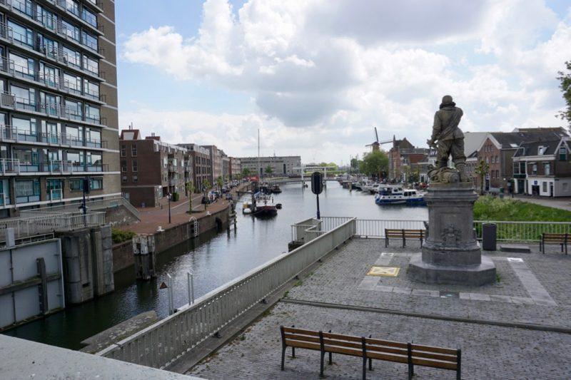 Het standbeeld van zeeheld Piet Hein kijkt uit over de Achterhaven van Delfshaven